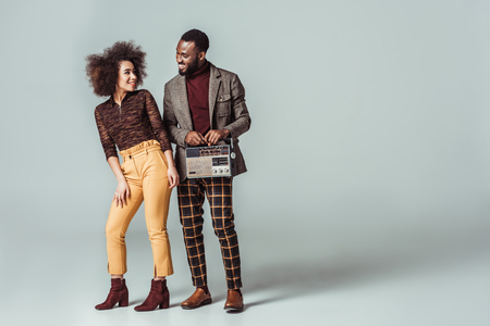 happy african american retro styled couple looking at each other with vintage radio on grey Stock Photo