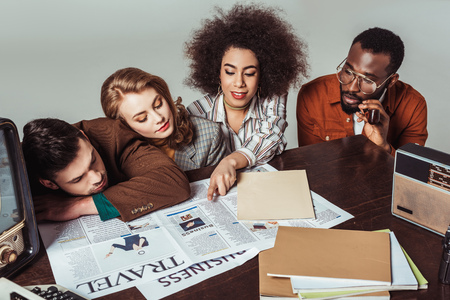 multicultural retro styled journalists reading newspapers isolated on grey