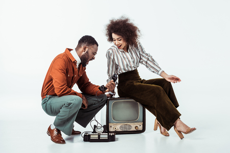 african american retro styled couple looking with surprise at vintage phone on white