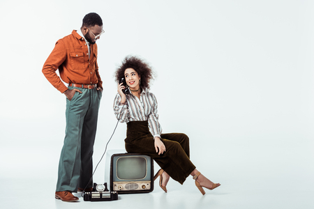 african american retro styled girlfriend sitting on vintage television and and talking by phone on white Stock Photo - 111844794