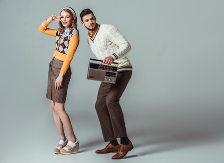 beautiful retro styled couple dancing with vintage radio on grey