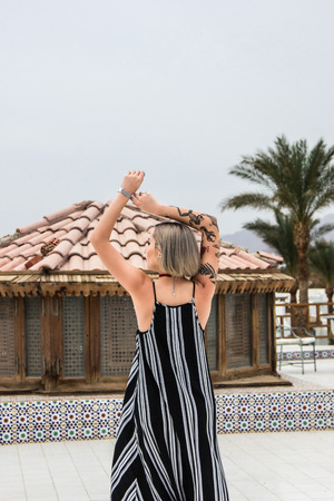 back view of young woman in dress posing with raised hands at resort in Egypt Stockfoto