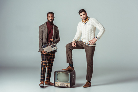multicultural retro styled friends posing with vintage radio and television on grey Stock Photo
