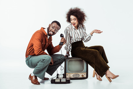 happy african american retro styled couple with vintage television and phone on white Stock Photo