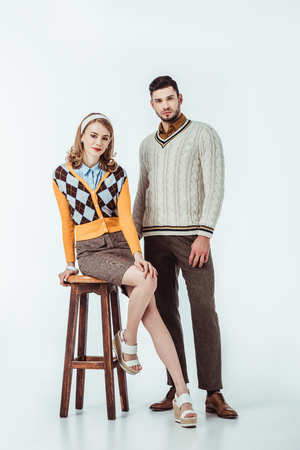 beautiful retro styled couple with wooden chair looking at camera on white