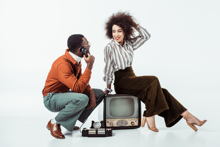 african american retro styled boyfriend talking by stationary phone on white Stock Photo