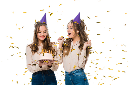 happy twins in birthday caps looking at birthday cake under falling confetti isolated on white