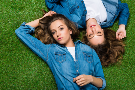 top view of attractive young twins lying on green grass
