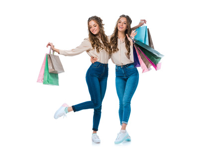 smiling young twins hugging with shopping bags isolated on white