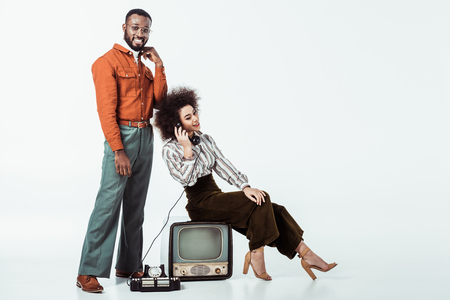 happy african american retro styled girlfriend sitting on vintage television and and talking by phone on white Stock Photo