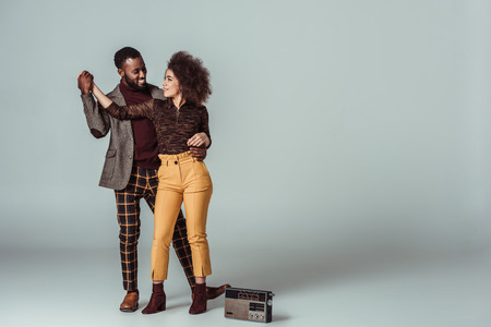 african american retro styled couple dancing on grey, vintage radio on floor