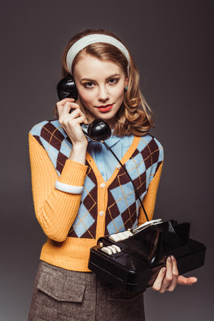 attractive retro styled girl talking by vintage stationary telephone isolated on grey