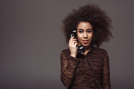 african american retro styled girl talking by vintage stationary telephone isolated on grey Imagens