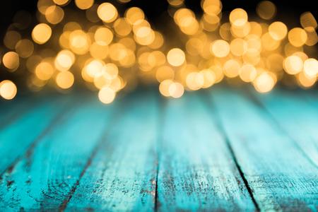 festive bokeh lights on blue wooden surface, christmas background Reklamní fotografie