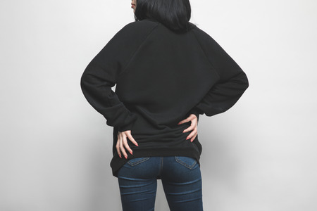 rear view of young woman in black hoodie on white