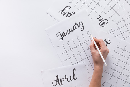 partial view of woman making notes in calendar isolated on white