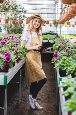 Female gardener with clipboard filling order of flowers in greenhouse