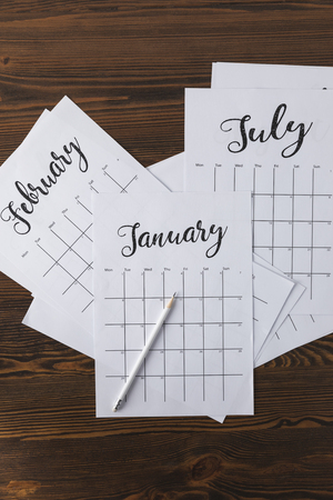 flat lay with arranged calendar papers and pencil on wooden tabletop Stockfoto - 111850873