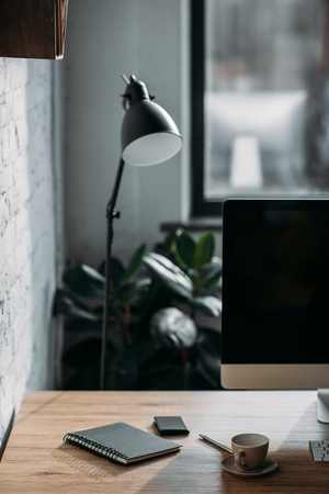 notebook with cup and table lamp on office table 스톡 콘텐츠