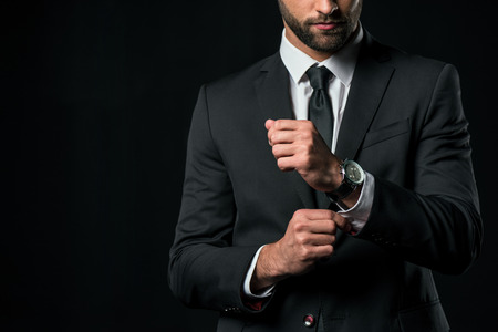 cropped view of businessman in jacket with wristwatch, isolated on black Archivio Fotografico