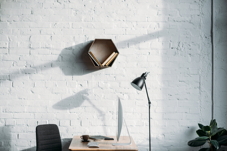 table lamp, computer and shelf on wall in office