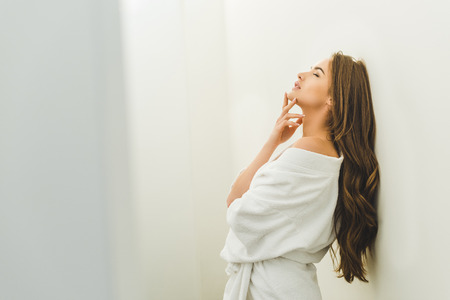 side view of attractive sensual woman in bathrobe at home