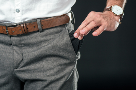 cropped view of poor businessman with empty pocket, isolated on black Banque d'images - 111851369