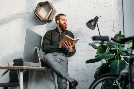businessman leaning on table, holding book and looking away