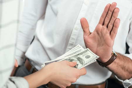 cropped view of businessman refusing to take bribe from partner, isolated on black Stock Photo