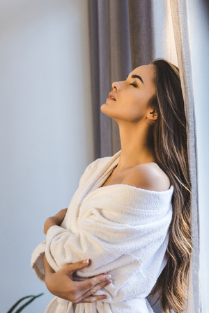 side view of attractive young woman in bathrobe at home