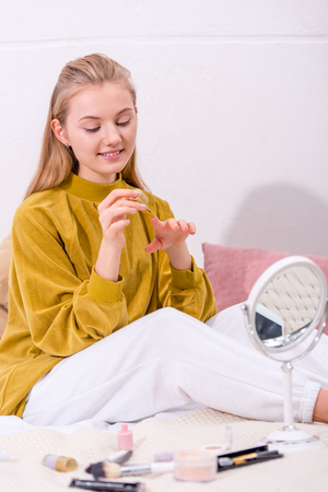 happy young woman polishing nails in bed at home