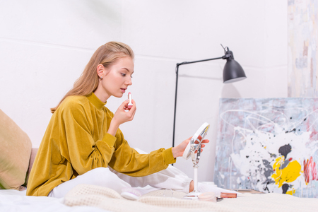 beautiful young woman applying lipstick on bed at home Stock Photo - 111854139