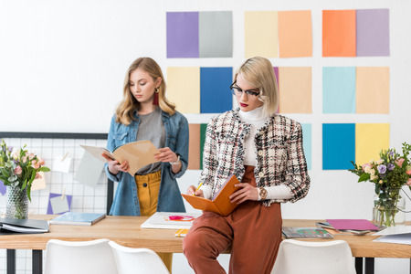 beautiful magazine editors doing paperwork in modern office with color palette