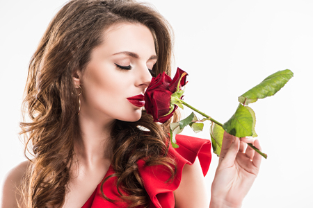 stylish girl sniffing rose with closed eyes isolated on white, valentines day concept