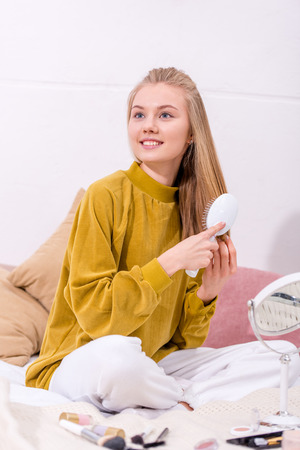 happy young woman brushing hair at home Stockfoto
