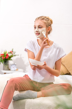 attractive woman applying clay mask on face while sitting on bed Foto de archivo - 111854277