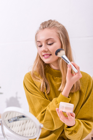 happy young woman applying blush and looking at mirror
