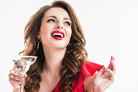 laughing beautiful woman holding glass of cocktail isolated on white