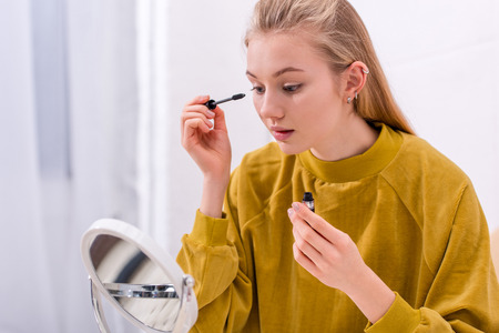 young woman applying mascara and looking at mirror Stock Photo - 111856378