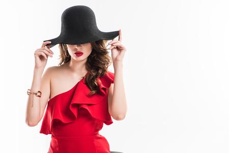 attraktives modisches Mädchen versteckt Augen unter schwarzem Hut isoliert auf weiß