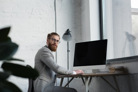 businessman sitting at table with computer and looking at camera Stock Photo