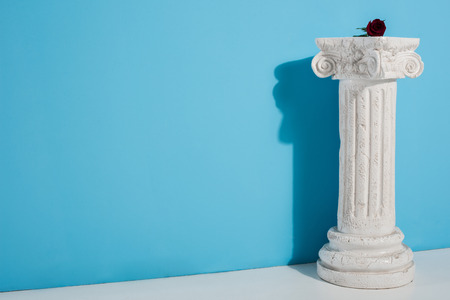 one red rose on white column on blue Stock Photo