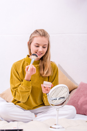 happy young woman applying blush