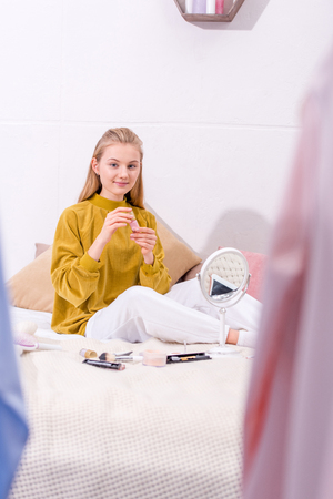 young woman doing makeup while sitting on bed at home Stock Photo
