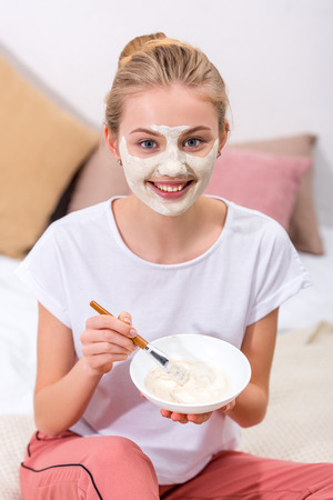 young woman applying clay mask on face at home and looking at camera