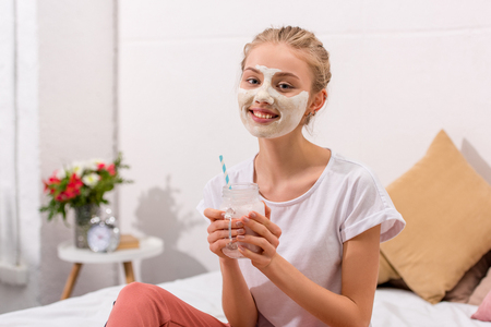 smiling young woman with white clay facial mask with milkshake in mason jar at home Foto de archivo - 111858131