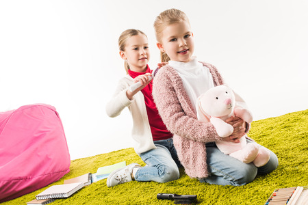 one sister brushing hair of another while she sitting on floor with toy bunny isolated on white