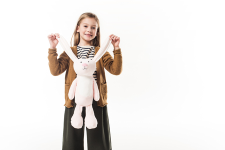 adorable little child holding soft toy bunny by ears isolated on white Standard-Bild - 111858417