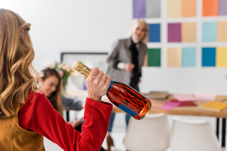 selective focus of magazine editors celebrating with champagne in modern office