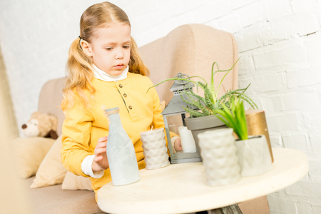 cute little child arranging objects on table during relocation